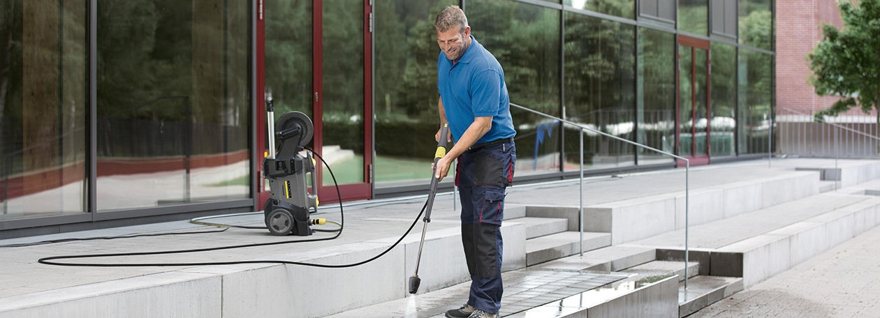 person cleaning steps with a small cold jet washer produced by karcher